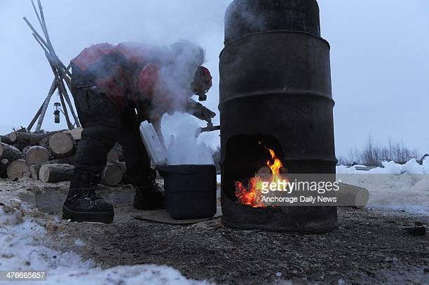 Aliy Zirkle fills her cooler with hot water to mix dog food at the Nikolai checkpoint during the 2014 Iditarod Trail Sled Dog Race on Tuesday March 4...