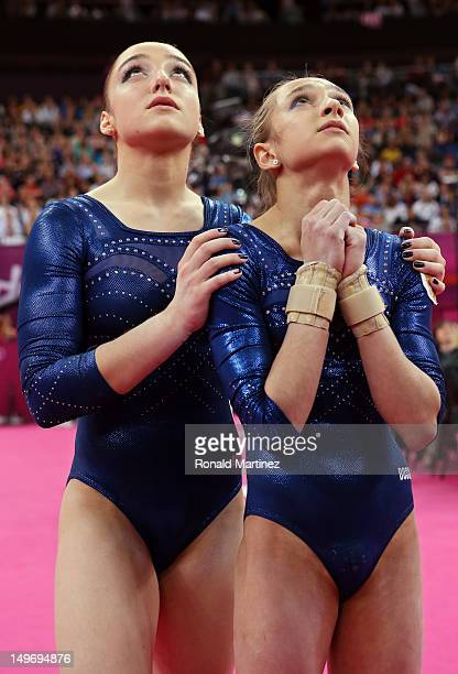 Aliya Mustafina and Victoria Komova of Russia wait for the final scores to be announced in the Artistic Gymnastics Women's Individual AllAround final...