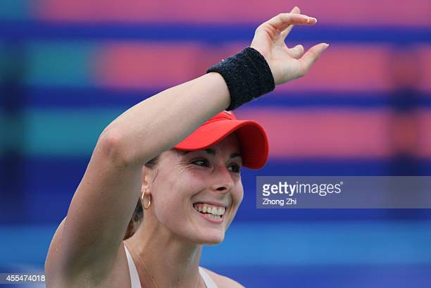 Alize Conrnet of France reacts after winning her match against Yulia Putintseva of Kazakhstan during day one of the 2014 WTA Guangzhou Open at Taint...