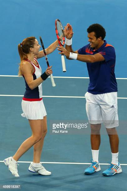 Alize Cornet and JoWilfried Tsonga of France celebrate defeating Sloane Stephens and John Isner of the United States in the mixed doubles match...