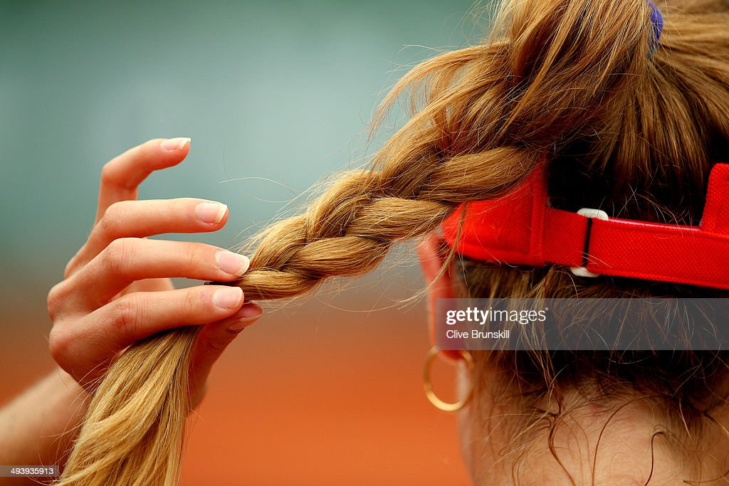 Alize Cornet of France adjusts her hair during a break in her women's singles match against Ashleigh Barty of Australia on day two of the French Open at Roland Garros on May 26, 2014 in Paris, France.