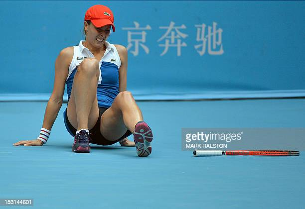 Alize Cornet of France falls to the ground during her women's singles match against World number one Victoria Azarenka of Belarus at the China Open...