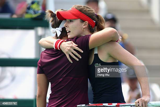 Alize Cornet of France hugs Kirsten Flipkens of Belgium after defeating Flipkins during day four of the 2014 Dongfeng Motor Wuhan Open at Wuhan...
