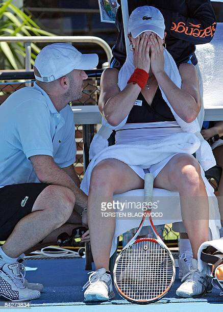 Alize Cornet of France listens to her coach Pierre Bouteyre before succumbing to the heatwave conditions and second seed Dinara Safina of Russia in...