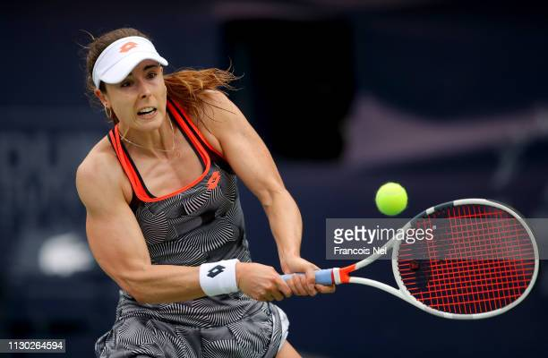 Alize Cornet of France plays a backhand in her match against Timea Babos of Hungary during day one of the WTA Dubai Duty Free Tennis Championships at...