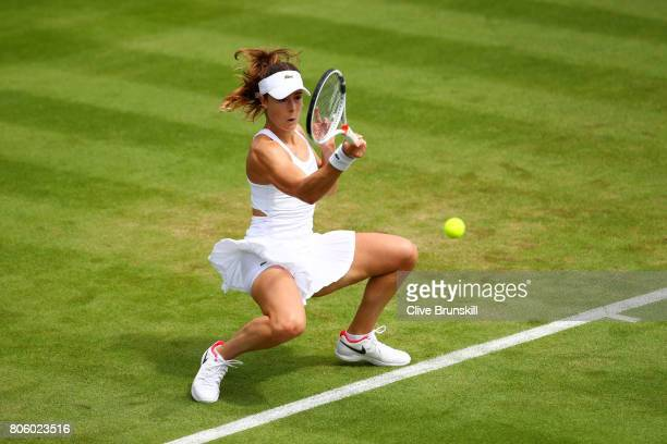 Alize Cornet of France plays a forehand during the Ladies Singles first round match against Camila Giorgi of Italy on day one of the Wimbledon Lawn...