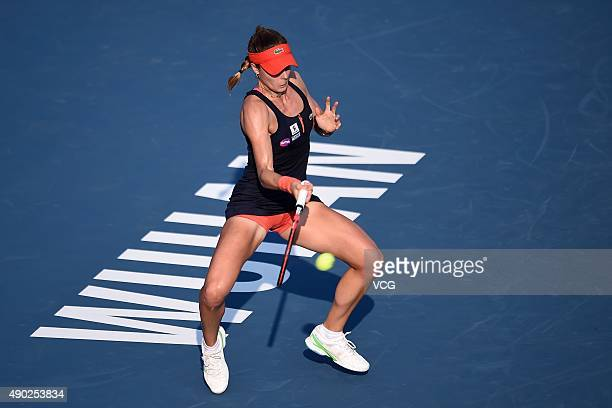 Alize Cornet of France returns a shot against Julia Goerges of Germany during a match in the first round of 2015 Wuhan Open at Optics Vally...