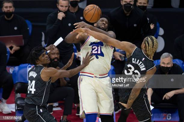 Alize Johnson and Nicolas Claxton of the Brooklyn Nets knock the ball out of the hands of Joel Embiid of the Philadelphia 76ers in the fourth quarter...