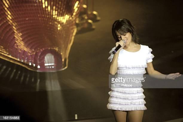 Alizee At The Olympia ALIZEE vêtue d'une mini robe blanche à volants chantant sur la scène de l'Olympia