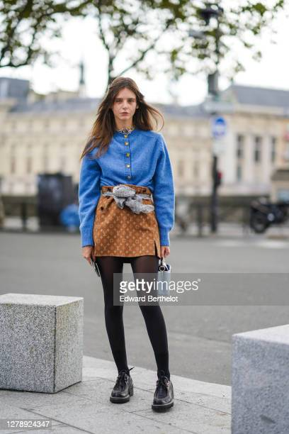 Alizee Gamberini wears a blue wool pullover with golden buttons, a brown monogram Vuitton skirt, black tights, brown leather monogram Vuitton shoes,...