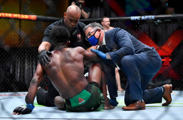 Aljamain Sterling is checked after receiving an illegal knee from Petr Yan of Russia in their UFC bantamweight championship fight during the UFC 259...