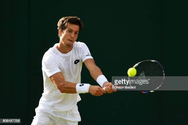 Aljaz Bedene of Great Britain plays a backhand during the Gentlemen's Singles first round match against Ivo Karlovic of Croatia on day one of the...