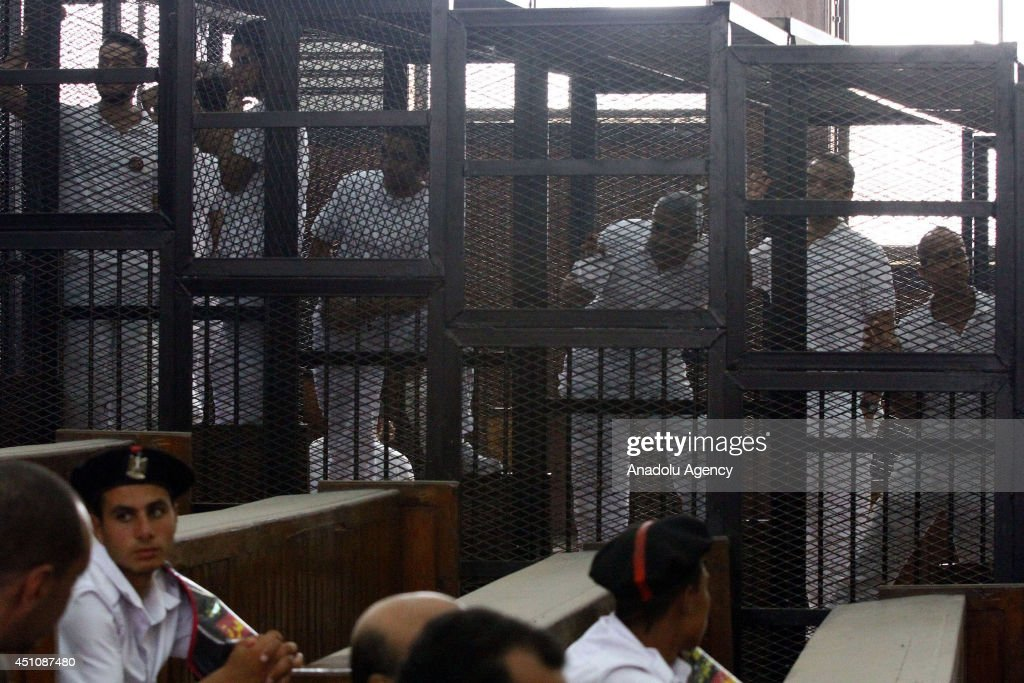 Al-Jazeera news channel's Australian journalist Peter Greste (R) and Egyptian-Canadian Mohamed Fadel Fahmy (R3) listen to the verdict inside the defendants cage during his trial for allegedly supporting the Muslim Brotherhood on June 23, 2014 at the police institute near Cairo's Tora prison.