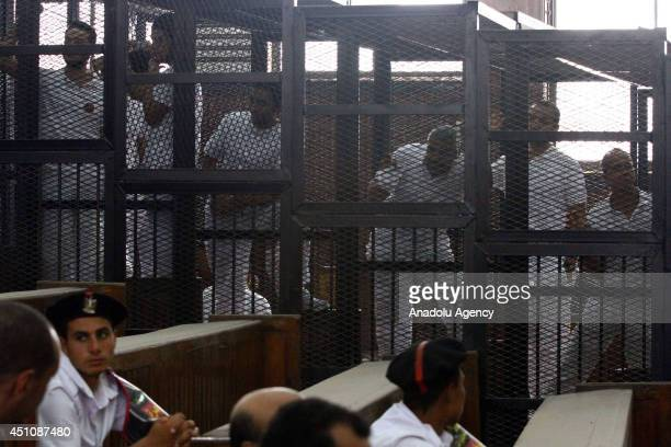 AlJazeera news channel's Australian journalist Peter Greste and EgyptianCanadian Mohamed Fadel Fahmy listen to the verdict inside the defendants cage...