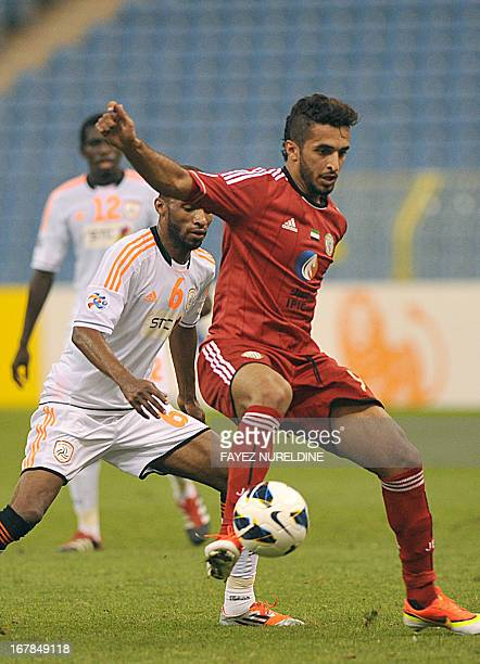 UAE alJazira player Ali Ahmed controls the ball in front of Saudi Arabia's alShabab club player Omar Alghamdi during their AFC Champions League group...