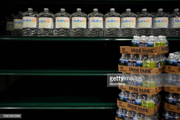 Alkaine water bottles sit next to empty shelves at a Harris Teeter grocery store ahead of Hurricane Florence in Greenville North Carolina US on...