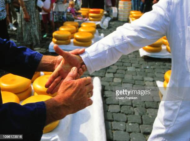 alkmaar holland cheese market. two friends shaking hands - image stockfoto's en -beelden