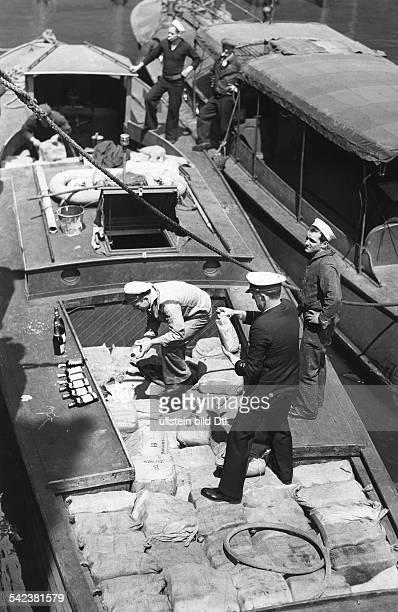 Alkohol Prohibition USA 19201933AlkoholschmuggelKontrollbeamte der Küstenwache entdecken bei der Prüfungeiner Schiffsladung versteckteSchnapsflaschen...