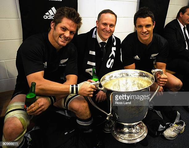All Black captain Richie McCaw holds the Bledisloe Cup with New Zealand Prime Minister John Key and Dan Carter in the dressing shed following the...