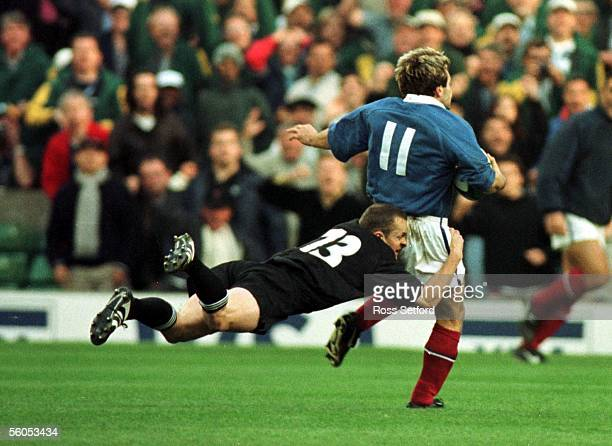 All Black Christian Cullen makes a diving tackle on France's Christophe Dominici in the semi final of the Rugby World Cup at Twickenham, London,...