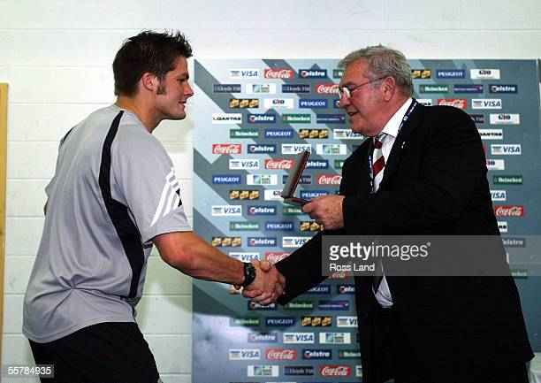 All Black flanker Richie McCaw shakes hands with IRB Chairman Sid Millar as he is presented with his 3rd place medallion following New Zealand's'...