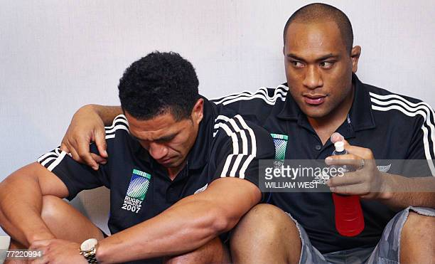 All Black fullback Mils Muliaina is comforted by teammate Neemia Tialata during a press conference in Cardiff 07 October 2007 The New Zealand All...