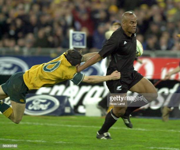 All Black Jonah Lomu fends off Wallaby Stephen Larkham on the the way to scoring the winning try in the Tri Nations match at Stadium Australia Sydney...