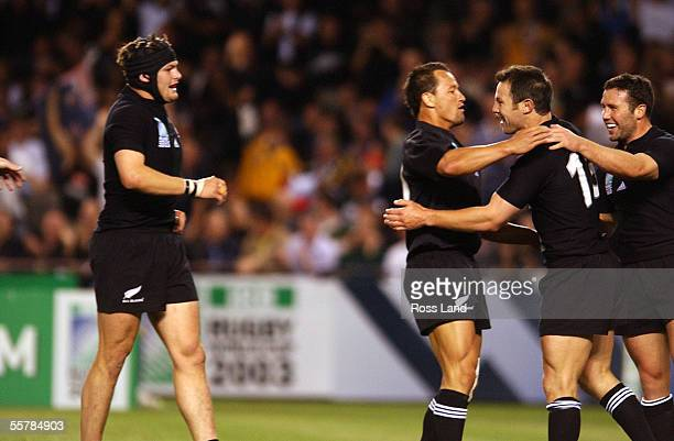 All Black Leon MacDonald is cangratulated by team mates Aaron Mauger Carlos Spencer and Richie McCaw after scoring the opening try for New Zealand...