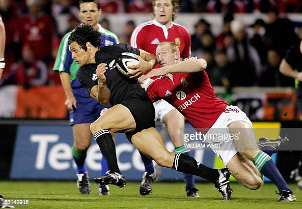 All Black winger Doug Howlett attempts to slip pass the tackle of British and Irish Lions counterpart Gareth Thomas during the first Test match in...