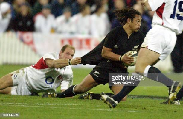 All Blacks Tana Umaga has Lawrence Dallaglio of England hanging from his shirt as he looks for support in the rugby test match at Westpac Stadium...