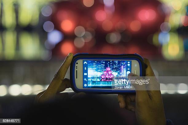 All Logo removed cellular camera phone is used to photograph Giant red ornaments lights on display along Sixth Avenue in midtown Manhattan for the...