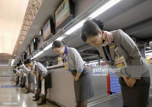 All Nippon Airways Co employees bow as they welcome passengers in front of checkin counters in Terminal 1 at Kansai International Airport on Sept 14...