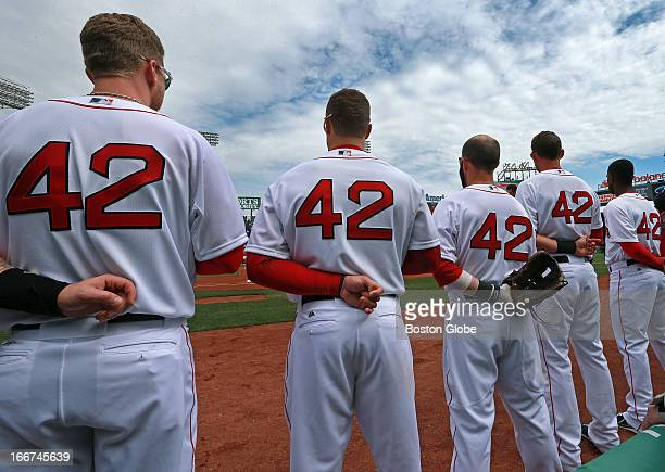 All players are wearing number 42 in honor of Jackie Robinson Day as the Boston Red Sox stand on the field lined up for the singing of the national...