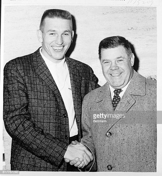 All smiles John Unitas star quarterback of the Baltimore Colts and Weeb Ewbank the World Champion Colts' coach shake hands before leaving for the...