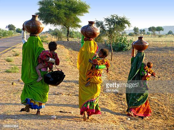 All three of these women are returning back to home after having their utensils filled with the water from the well or the water reservoir situated...