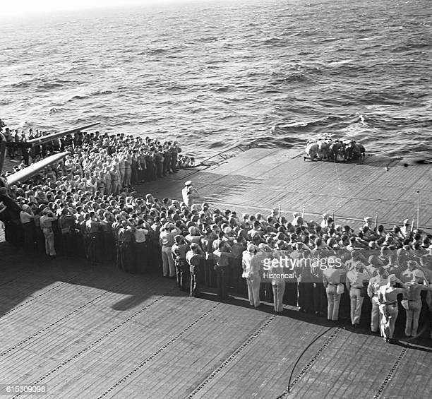 All USS Lexington hands stand at attention as two of their fellow crewmen are buried at sea November 1943 | Location USS Lexington