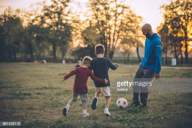 all we need is a soccer ball and part of green field - son stock pictures, royalty-free photos & images