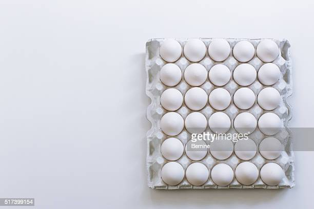 all white carton of eggs on white table - carton stock pictures, royalty-free photos & images