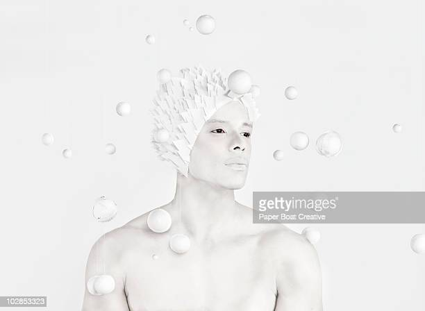 All white image of a man in the center of planets