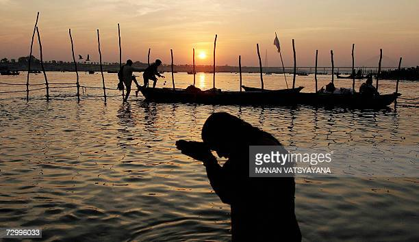 In Indian Hindu takes a ritual bath at Sangam the confluence of the Ganges Yamuna and Saraswati rivers in Allahabad 14 January 2007 during the Ardh...
