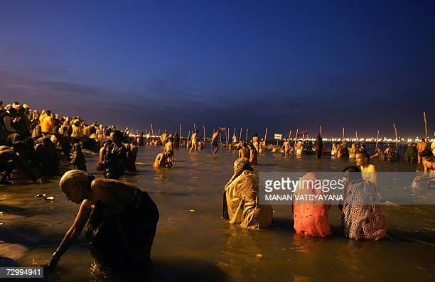 Indian Hindu devotees take holy bath at Sangam the confluence of the Ganges Yamuna and Saraswati rivers in Allahabad early morning on 14 January 2007...