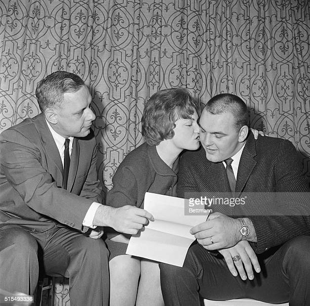 All-American Center Dick Butkus of Illinois gets a big kiss from his wife Helen after signing with Chicago Bears here 12/3, as George Halas, Jr.,...