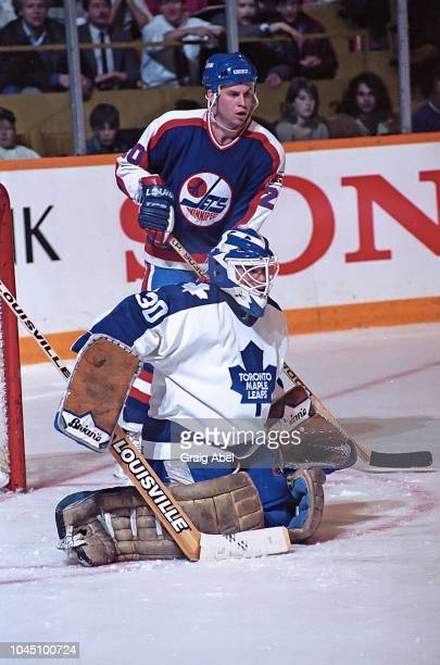 Allan Bester of the Toronto Maple Leafs skates against Dave McLlwain the Winnipeg Jets during NHL game action on March 17 1990 at Air Canada Centre...