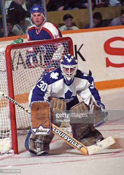 Allan Bester of the Toronto Maple Leafs skates Dave McLlwain of against the Winnipeg Jets during NHL game action on March 17 1990 at Air Canada...