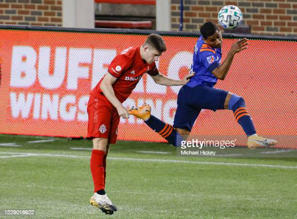 Allan Cruz of FC Cincinnati heads the ball as Liam Fraser of Toronto FC defends during the second half at Nippert Stadium on October 11, 2020 in...