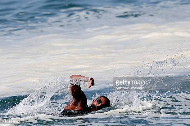 Allan do Carmo of Brazil swims through foam in the water on the course at Copacabana Beach during the Marathon Swimming Challenge Aquece Rio Test...