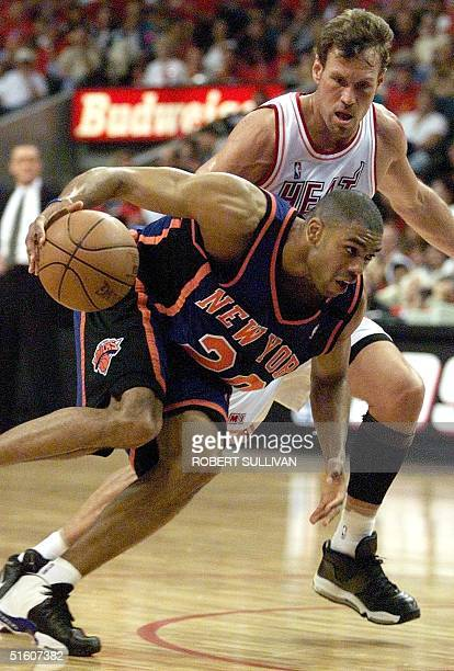 Allan Houston of the New York Knicks drives to the basket past Dan Majerle of the Miami Heat in first half action 16 May 1999 during game five of...