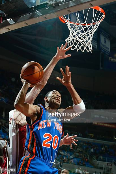 Allan Houston of the New York Knicks goes up for a shot against Zydrunas Ilgauskas of the Cleveland Cavaliers in NBA action at Gund Arena November 11...
