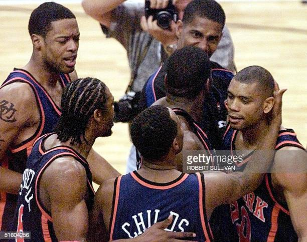 Allan Houston of the New York Knicks is congratulated by teammates after he made a lastsecond shot to beat the Miami Heat 16 May 1999 during game...