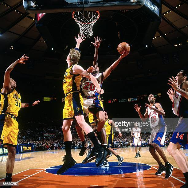 Allan Houston of the New York Knicks shoots a layup against Rik Smits of the Indiana Pacers in Game Three of the Eastern Conference Finals during the...